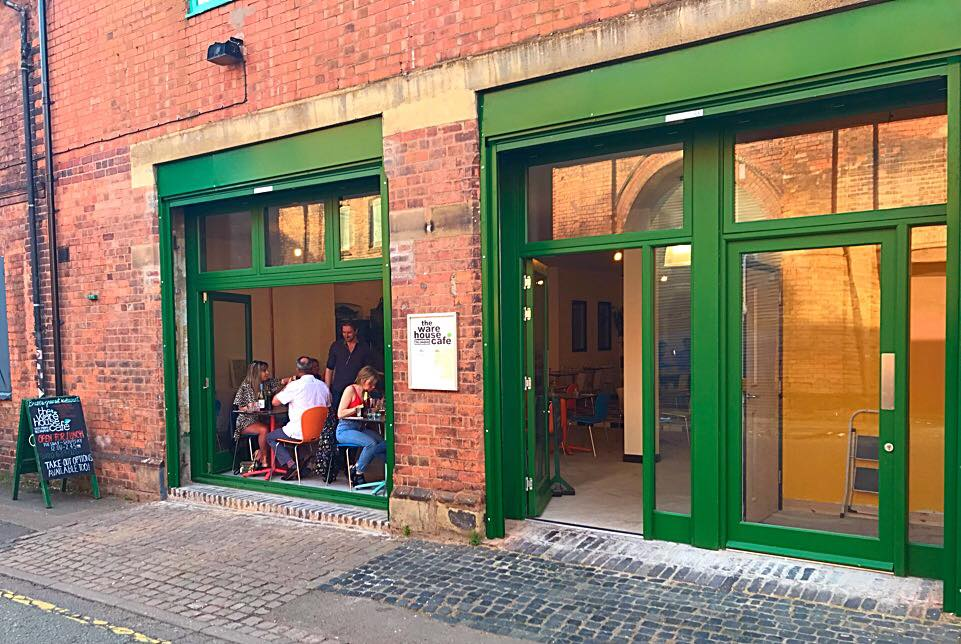 A photo of the outside of the Warehouse Cafe with customers enjoying their meals visible through the open windows